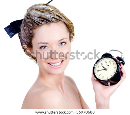 Close-up portrait of beautiful young woman with attractive smile coloring hair and holding alarm - isolated - stock photo