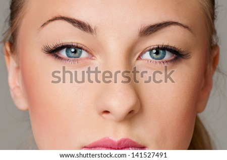 Close up portrait of beautiful young woman with blue eyes - stock photo