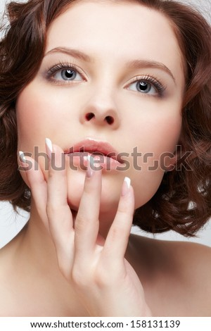 close-up portrait of beautiful young woman with french manicure - stock photo