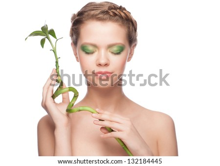 Close-up portrait of beautiful young woman with green bamboo. Isolated on white background - stock photo
