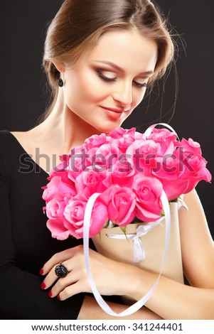 Close-up portrait of beautiful young woman with luxury jewelry and perfect make up holding bouquet. Fashion beauty portrait