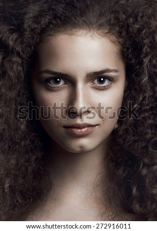 Close-up portrait of beautiful young woman with nice brown long curly hair looking at camera. Studio shot. Professional make-up and hair style. Color image - stock photo