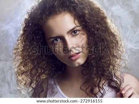 Close-up portrait of beautiful young woman with nice brown long curly hair looking at camera. Studio shot with back lights and smoke. Professional make-up and hair style.