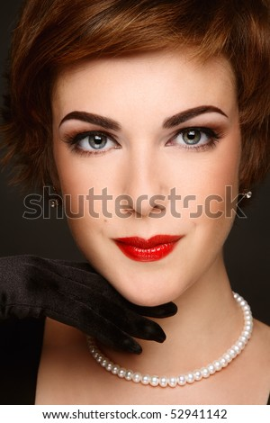 Close-up portrait of beautiful young woman with stylish makeup and pearl necklace