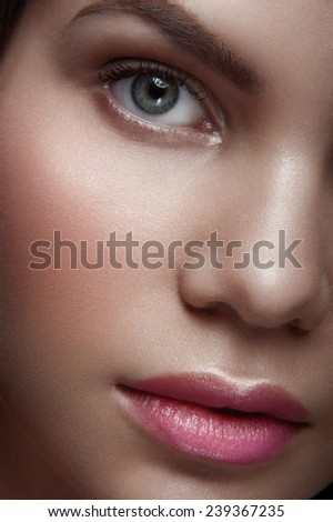 Close up portrait of beauty nude young lady with green eyes, natural make-up and natural lipstick, withhead to the right looking at you on dark background