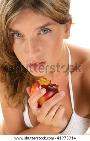 Close-up portrait of beauty woman holding ripe nectarine with bite - stock photo