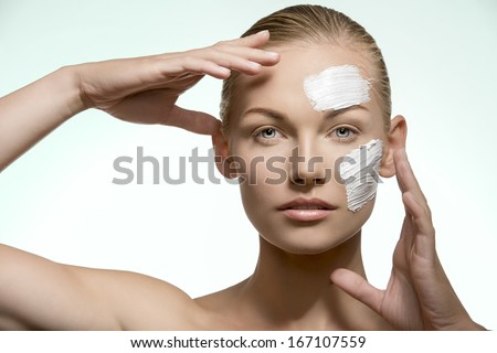 close-up portrait of beauty woman with blonde tied back hair, natural look, applying cream treatment on her visage. Skin care  - stock photo