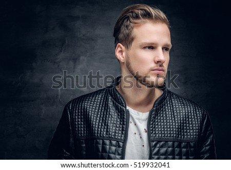 Close up portrait of blond bearded male dressed in a black leather jacket.