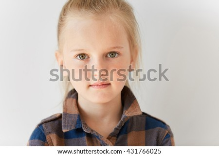 Close up portrait of blond European female child. Little kid with green eyes staring at camera in morning light indoors. Cute isolated appearance and relaxed innocent look. - stock photo