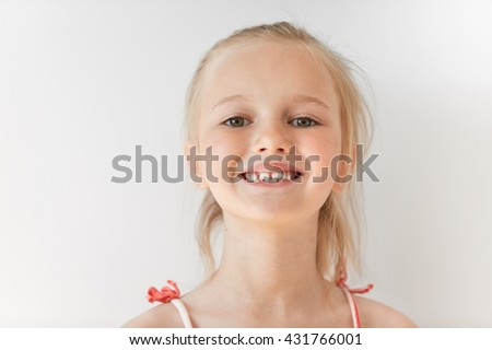 Close-up portrait of blond European little girl smiling with all her teeth. Happy kid in sunny afternoon makes every parent feel good. Childish smile is a source of positive emotions. - stock photo
