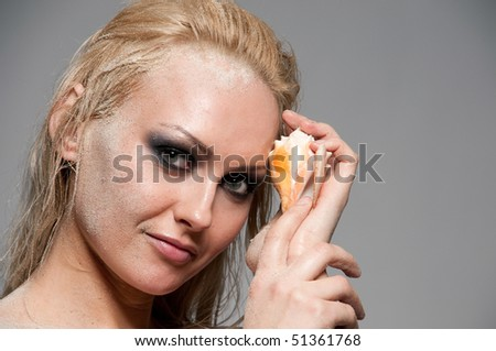Close up portrait of blond woman with smoky eyes makeup, sand and shell