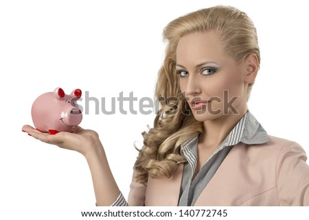 close-up portrait of blonde girl with business suit and curly hair-style taking pink piggybank in the hand and looking in the camera