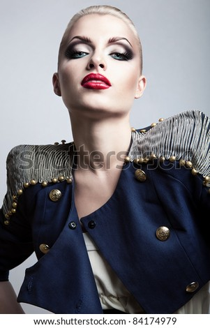 close-up portrait of blonde woman in blue jacket with red lips - stock photo
