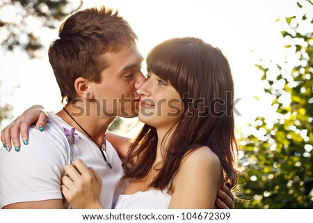 Close up portrait of boy kissing girlfriend on cheek outdoors - stock photo