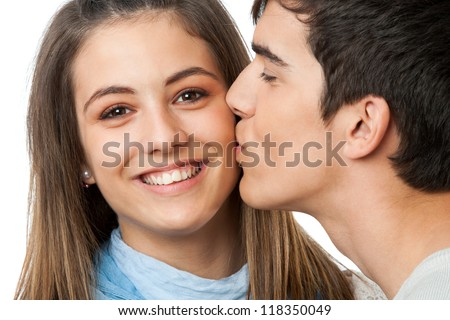 Close up portrait of boyfriend kissing girlfriend on cheek.Isolated on white. - stock photo