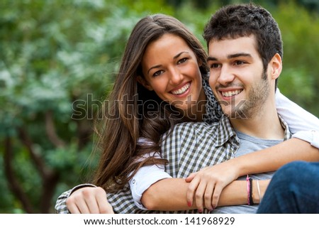 Close up portrait of brunette and her boyfriend in park. - stock photo