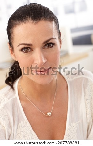Close up portrait of brunette casual smiling businesswoman at office. - stock photo