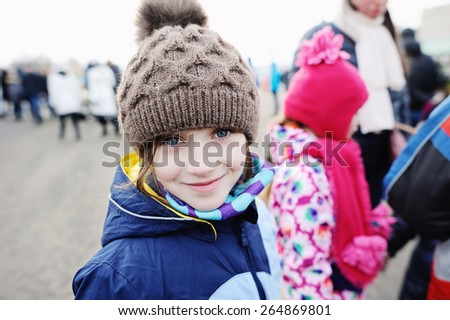 Close-up portrait of brunette child gir in scarf and blue jacket - stock photo
