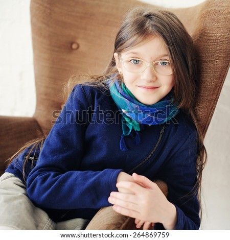 Close-up portrait of brunette child gir in scarf and blue jacket in glasses - stock photo