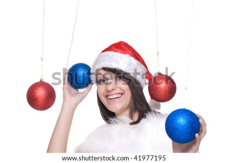 Close up portrait of brunette girl in santa claus dress, white fur playing with decoration balls