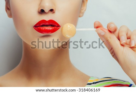 close-up portrait of brunette woman portrait with red lips and big eyes are brown. candy on a stick lollipop - stock photo