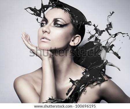 close up portrait of brunette woman with black splash - stock photo
