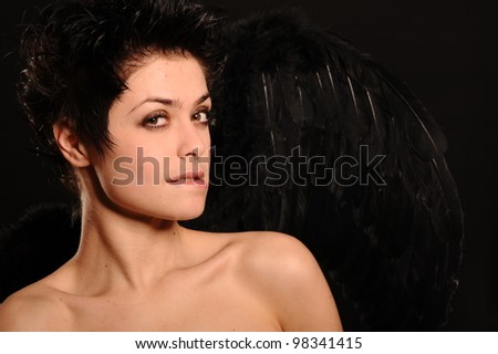 close up portrait of brunette woman with wings, isolated on black - stock photo