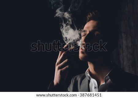 Close up portrait of brutal man in the smoke holding a cigar - stock photo