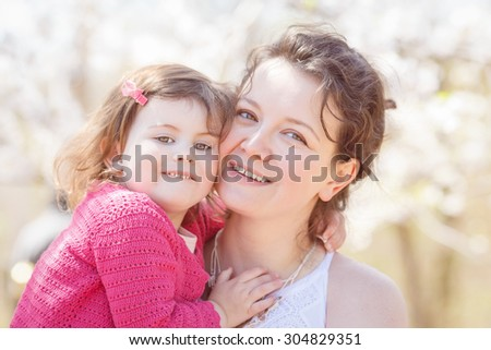 Close up portrait of caucasian mother in white dress holding hugging her daughter in pink clothes  kissing her in cheek on sunny spring summer day in the park outside  - stock photo