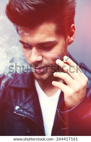 Close up portrait of charming fashionable man exhaling cigarette smoke while looking down, trendy attractive man blowing smoke out of his mouth standing on grey background, filtered image, red flare - stock photo