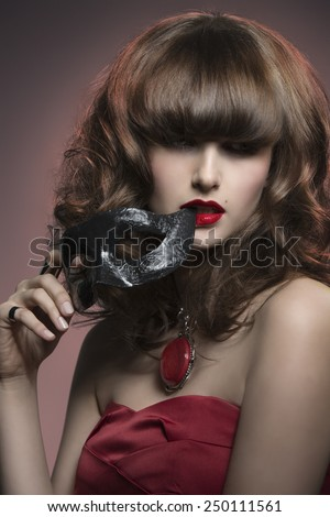 close-up portrait of charming woman with red dress, cute hair-style and black mask in the hand, mysterious style