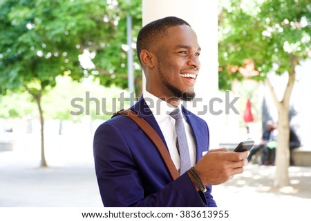 Close up portrait of cheerful young african businessman with cell phone in the city