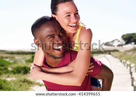 Close up portrait of cheerful young man carrying beautiful girlfriend on his back - stock photo