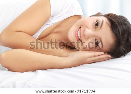 close up Portrait of cheerful young woman smiling while lying down on bed - stock photo