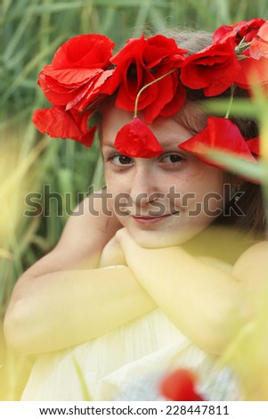 close up portrait of child girl with circlet of poppies sitting at the grass  - stock photo