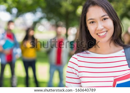 Close-up portrait of college girl with blurred students standing in the park - stock photo