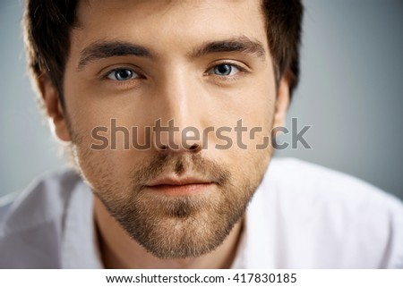 Close up portrait of confident elegant handsome young businessman in white shirt looking at camera. Studio, isolated on grey background. - stock photo