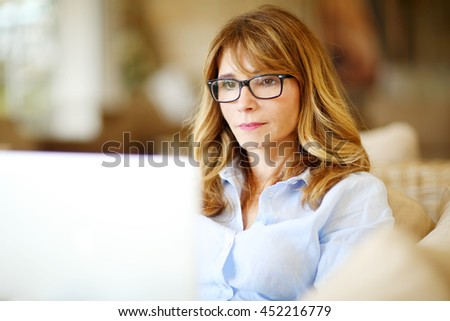 Close-up portrait of confident middle aged businesswoman using her laptop while working at home.  - stock photo