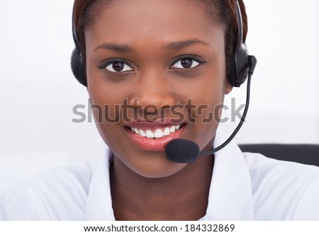 Close-up portrait of confident receptionist using headset in hospital - stock photo