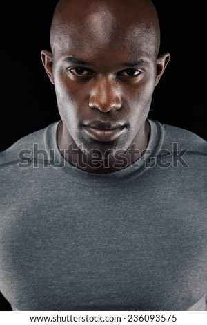 Close-up portrait of confident young african man against black background - stock photo