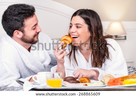Close up portrait of couple having fun at breakfast in hotel room.Girl about to take bite of croissant. - stock photo