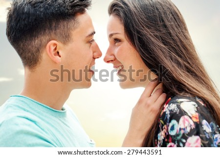 Close up portrait of couple showing affection in late afternoon sun. - stock photo