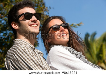 Close up portrait of couple with sunglasses on sunny day outdoors. - stock photo