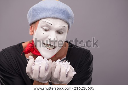 Close-up portrait of crazy male mime with grey hat and white face holding crumped paper and looking at this paper with interest isolated on grey background