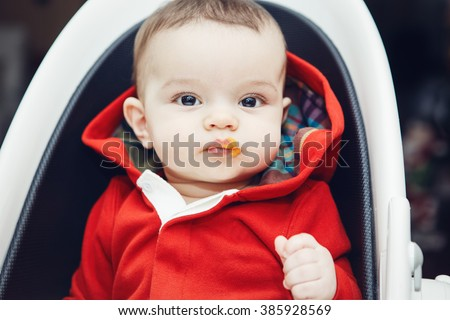 Close-up portrait of cute adorable Caucasian little baby boy with dark black eyes sitting in high chair in kitchen looking in camera eating meal puree - stock photo