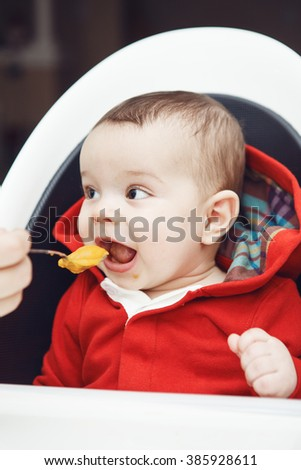 Close-up portrait of cute adorable Caucasian little baby boy with dark black eyes sitting in high chair in kitchen looking away, eating meal puree, mother feeds her son - stock photo