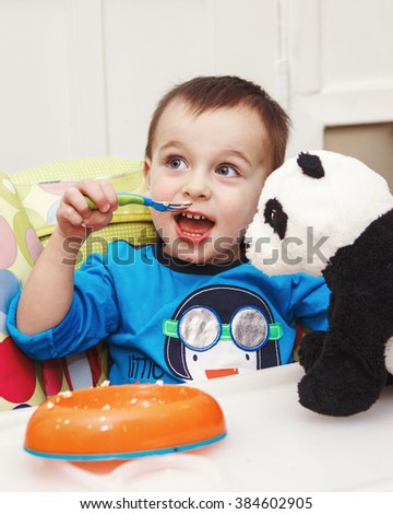 Close-up portrait of cute adorable little boy toddler two years old sitting in high chair in kitchen eating meal lunch dinner using fork and feeding his panda soft plush toy - stock photo