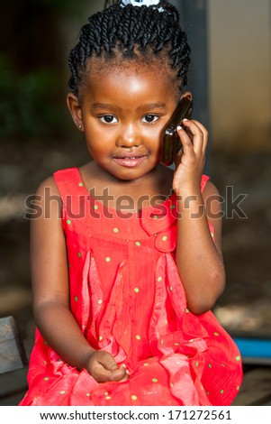 Close up portrait of cute african girl talking on cell phone outdoors. - stock photo