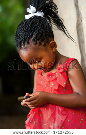 Close up portrait of cute african girl with braided hair playing on smart phone. - stock photo