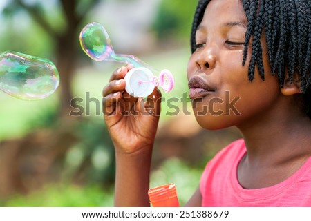 Close up portrait of cute African girl with braids blowing bubbles in park.